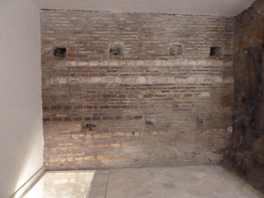 Fig. 9. Via Taddei: ambiente sotterraneo con le mura urbane (a dex.) e il tratto di lastricato stradale (a sin.)